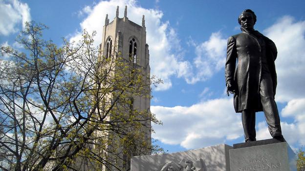 Auf dem Bild sieht man ein Denkmal des ukrainischen Dichters Taras Schewtschenko, vor blauem Himmel und einem Kirchturm.