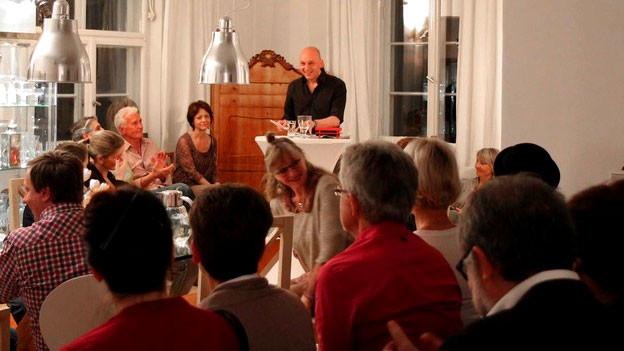 Menschen sitzen in einem Wohnzimmer, einn Autor liest.