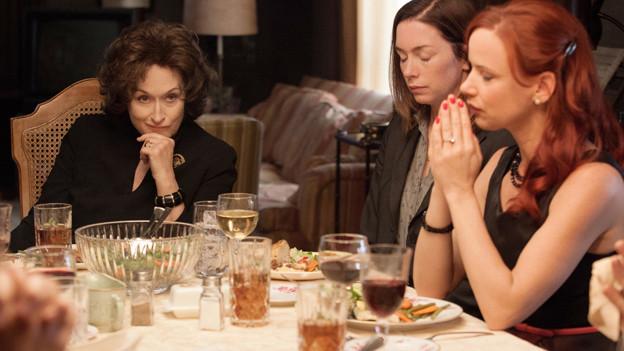 Eine Szene aus dem Kinofilm Osage County: Drei Frauen sitzen an einem gedeckten Tisch.