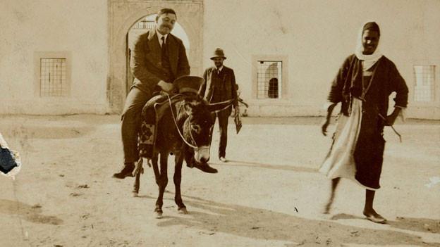 Mann auf Esel, Eselsführer, vor Moschee.