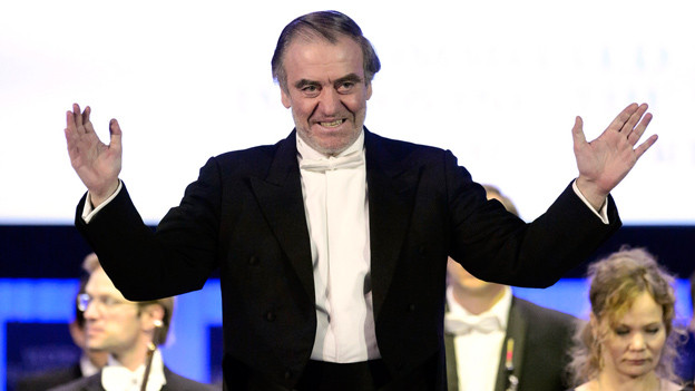 Ein Mann hält beide Arme ausgestreckt nach links und rechts und lächelt.