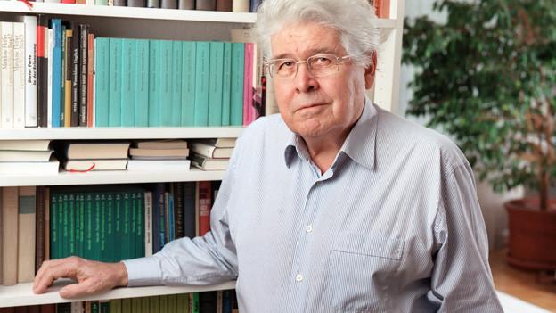 Der Filmemachter Alexander J. Seiler in einem Porträt vor einem Bücherregal.