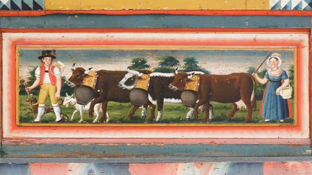 Malerei auf einem Holzkasten: Alpaufzug mit drei Kühenund einem Mann und einer Frau in Tracht