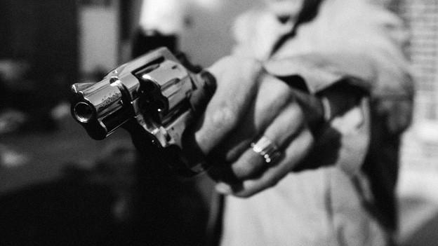 Symbolbild: Ein schwarz-weisses Bild zeigt eine ausgestreckte Hand, die einen Revolver hält.
