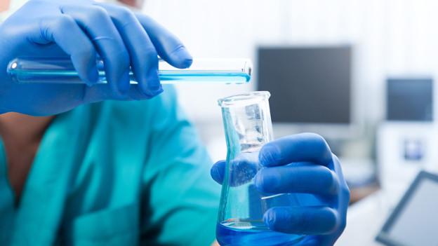 Das Bild zeigt zwei Hände mit blauen Latexhandschuhen, die ein Reagenzglas füllen.