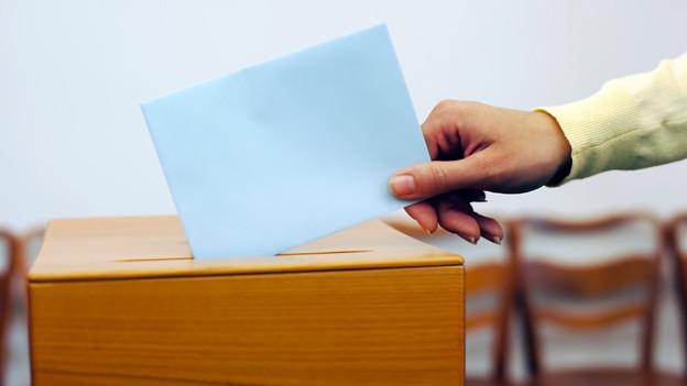 Das Bild zeigt eine weibliche Hand, die einen Brief in eine Abstimmungsurne wirft.