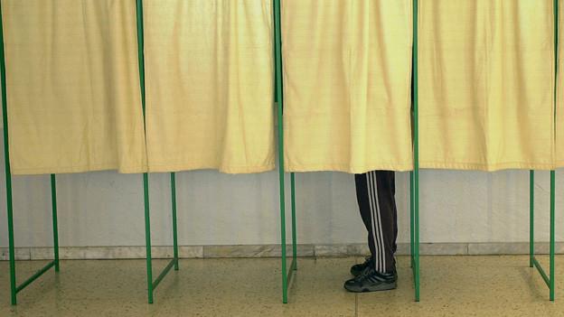 Das Bild zeigt einige Kabinen in einem Wahllokal, nur eine ist besetzt.