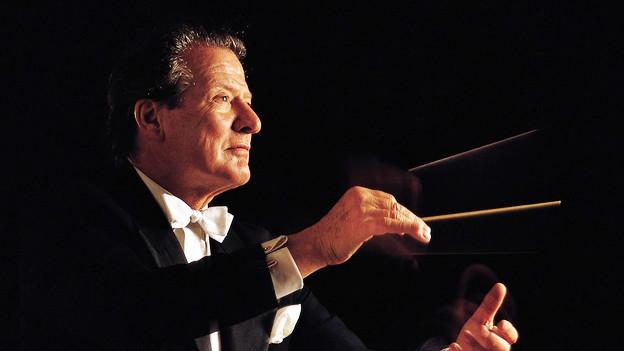 Das Bild zeigt den Dirigenten Sir Neville Marriner, vor dunklem Hintergrund den Dirigentenstab schwingend.