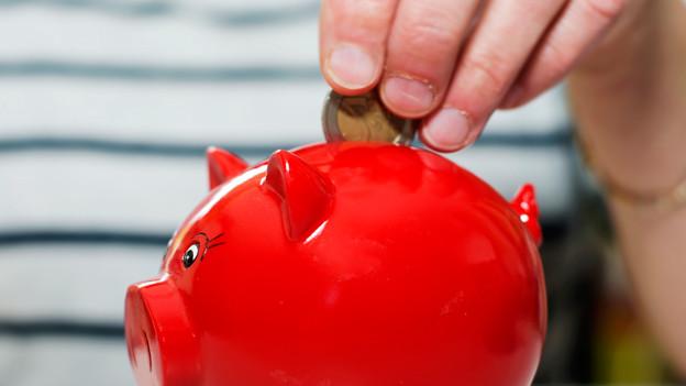 Das Bild zeigt ein rotes Sparschwein, in das eine Hand eine Münze wirft.