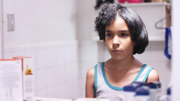 Ein junge steht vor dem Spiegel, seine Haare sind auf der einen Seite gekraust, auf der anderen glatt.