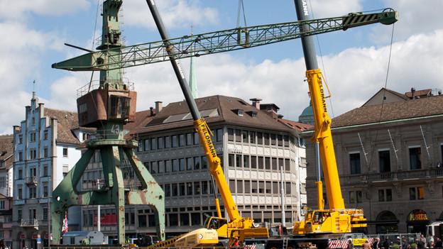 Die Fotografie zeigt einen grünlich-rostigen Hafenkran, der von modernen Kränen aufgebaut wird.