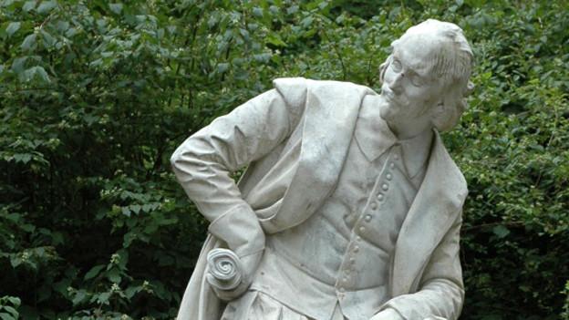Das Bild zeigt ein Denkmal von William Shakespeare, es ist aus weissem Stein gehauen und zeigt ihn sitzend.