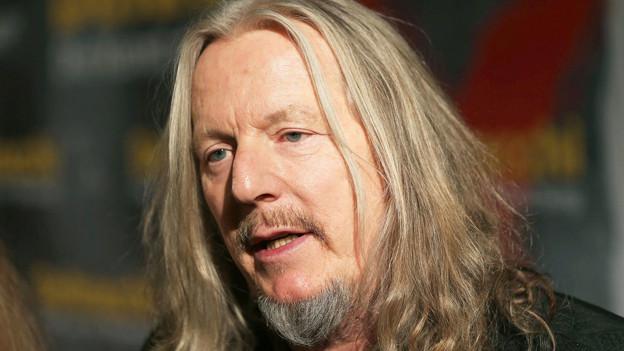 Das Porträt von Wolfgang Beltracchi zeigt einen Mann mittleren Alters mit langen, grau-blonden Haaren und Ziegenbart.