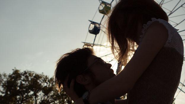 Das Bild zeigt zwei sich umarmende Personen vor einem Riesenrad.