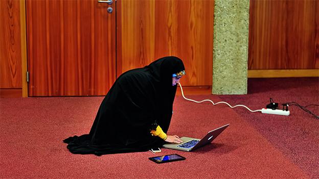 Eine Frau mit Kopftuch sitzt auf einem Teppichboden und schaut auf einen Laptop