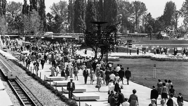 Die schwarz-weisse Fotografie zeigt das Areal der Expo 64 in Lausanne, auf dem viele Menschen flanieren zwischen Bäumen, Wiesen und hellen Wegen.