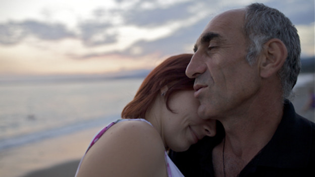 Ein Paar am Strand: Die Frau lehnt sich an der Schulter des Mannes an