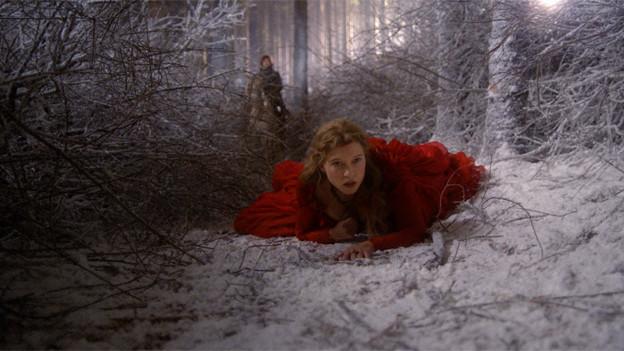 Eine Frau in rotem Kleid liegt in einem verschneiten Wald am Boden