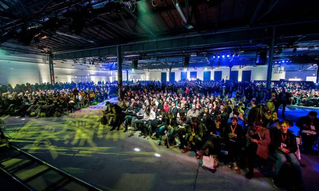 Die Fotografie zeigt eine bunt beleuchtete Halle voller Menschen, die in Richtung einer Bühne schauen.