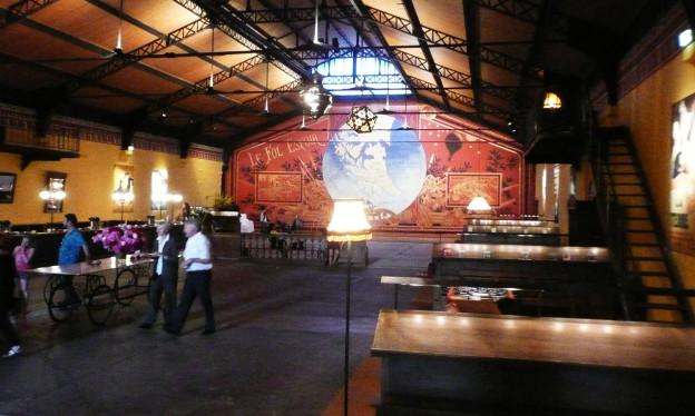In einem länglichen Raum ist ein Bühnenbild mit einer aufgemalten Weltkugel zu sehen.