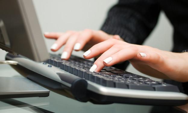 Zwei Frauenhände tippen auf eine Tastatur.