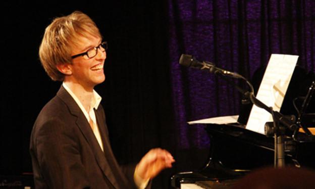 Ein junger Mann mit blonden Haaren sitzt am Klavier und lacht.