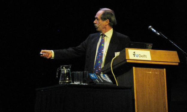 Ein Mann mittleren Alters steht vor einem Rednerpult und zeigt auf etwas, das man nicht sieht.
