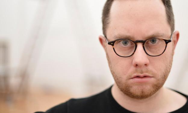 Das Porträt eines Mannes mit kurzen Haaren, Brille und Dreitagebart.