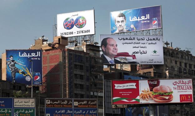 An Häuserwänden prangen Werbeplakate von Präsidentschaftskandidaten.