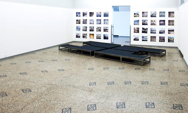 Der Innenraum des Kunstmuseums Solothurn mit Bildern an der Wand und einer flachen, schwarzen Installation am Boden.