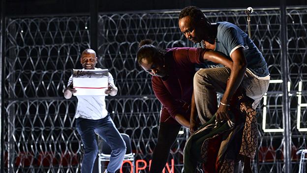 Bühnenszene: Im Vordergrund hilft eine Frau einem Mann, in eine Hose zu steigen.