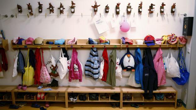 Eine Garderobe mit Kinderjacken und Rucksäcken.
