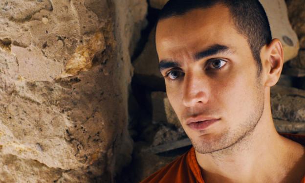 Das Bild zeigt das Porträt eines jungen Mannes vor einer Mauer, mit kurzen dunklen Haaren.
