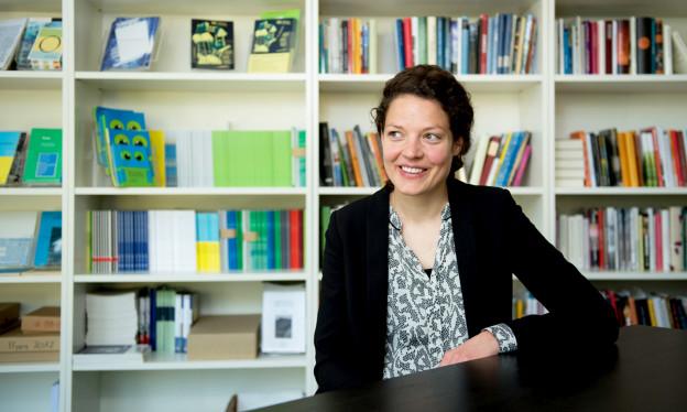 Eine junge Frau mit dunklen Haaren sitzt vor einem vollen Bücherregal.