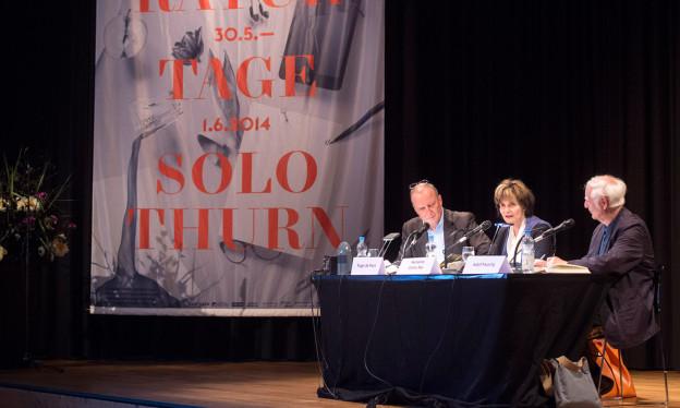 Drei Personen sitzen auf einer Bühne am Tisch und diskutieren.