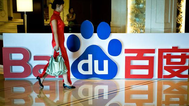 Eine Chinesin spaziert am Firmenlogo von Baidu vorbei.