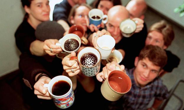 Einige junge Menschen stehen zusammen und halten ihre Kaffeetassen in die Höhe.