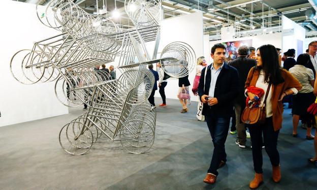 Eine Menschenmenge läuft in den Messehallen an Kunstwerken vorbei.
