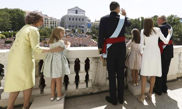Die spanische Königsfamilie steht auf einem Balkon und winkt zum Volk.