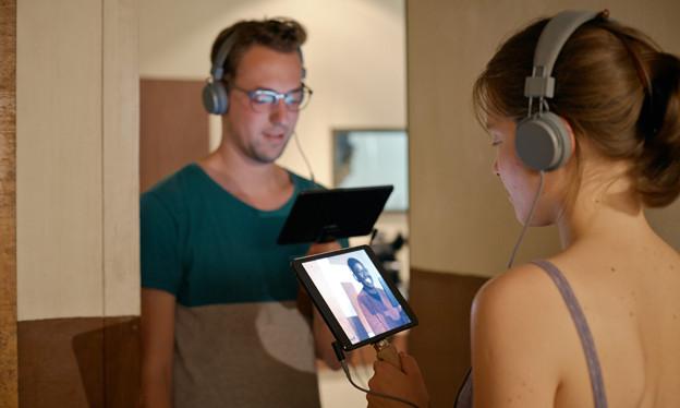 Zwei Personen mit Kopfhörern und Tablets.