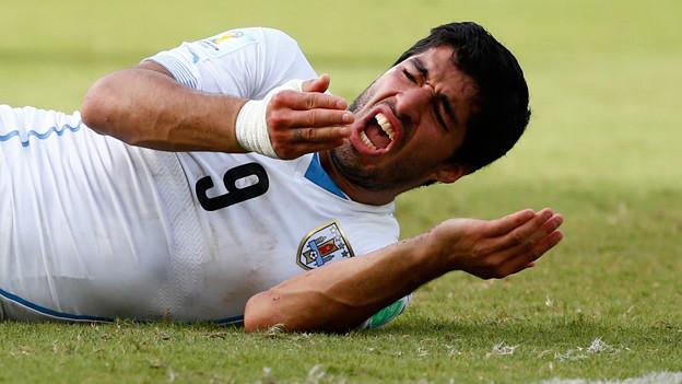 Ein Fussballer liegt mit offenen Mund auf dem Rasen.