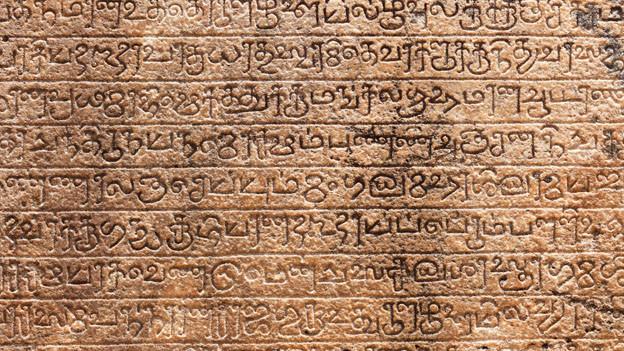 Eine alt anmutende Steintafel mit eingemeisselter Schrift.