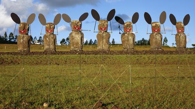 Eine Reihe von Osterhasen aus Stein steht auf einer Wiese.