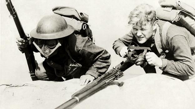 Zwei Soldaten im Ersten Weltkrieg liegen am Boden, der eine mit der Gasmaske bereits auf dem Gesicht, der andere zieht sie gerade an.