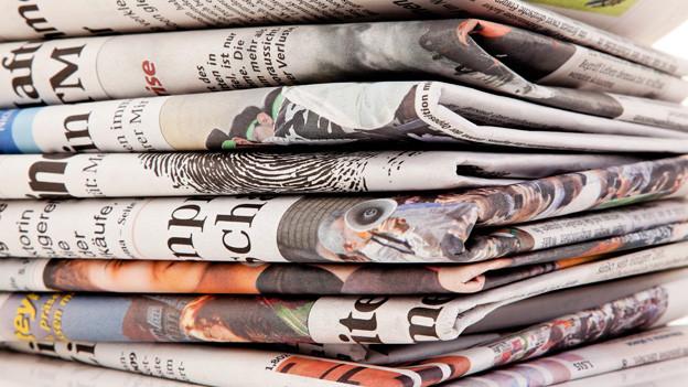 Ein Stapel mit Tageszeitungen.
