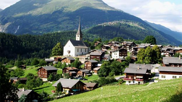 Die Ansicht eines kleinen Bergdorfes mit Kirche, Berge im Hintergrund.