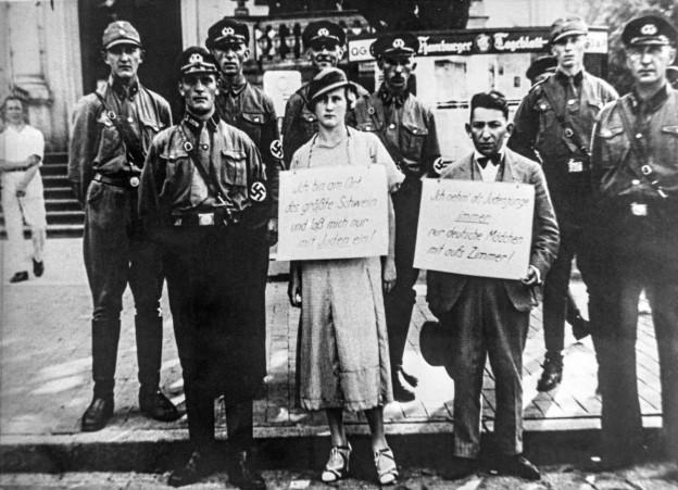 Ein Mann und eine Frau tragen Schilder mit Parolen, die sie selbst diffamieren. Im Hintergrund Nazi-Polizisten.