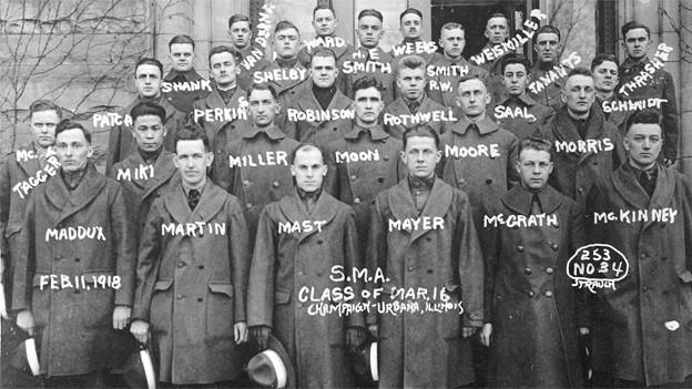 Eine schwarz-weisse Fotografie zeigt eine Gruppe junger Soldaten, das Foto ist angeschrieben mit deren Namen.