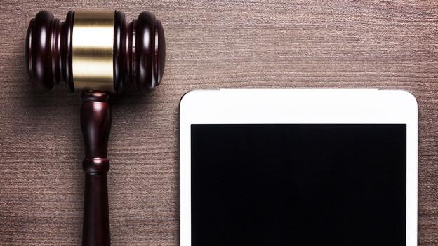 Ein Richterhammer liegt neben einem weissen Tablet.