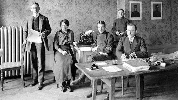 Fünf Personen sitzen und stehen in einem Raum und schauen in die Kamera.